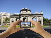 Tourist Holds Up Camera Phone At  Puerta De Alcala In Madrid