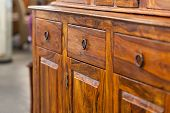 image of thrift store  - A closeup od a dark brown wooden cabinet with drawers - JPG