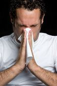 foto of snot  - Young sick man blowing his nose over black - JPG