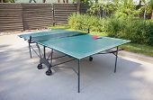 pic of ping pong  - Green ping pong table and rackets outdoors - JPG
