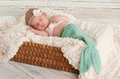 image of mermaid  - 2 week old newborn baby girl wearing a crocheted turquoise and pink mermaid costume sleeping in a basket with a bleached wood background - JPG