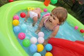 picture of inflatable slide  - Cute little girl having fun in the inflatable kids pool in the garden - JPG