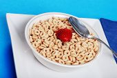 Bowl Of Cereal With A Strawberry And Spoon