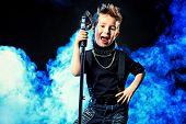 Emotional little boy is singing into a microphone like a rock musician.