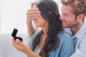 stock photo of rings  - Man hiding his wifes eyes to offer her an engagement ring for a marriage proposal - JPG