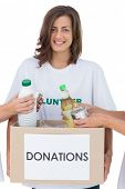 Smiling volunteer holding a food donation box on white background