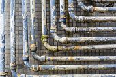 Series of parallel old pipes on wall