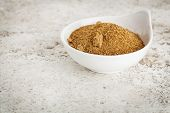 small ceramic bowl of unrefined coconut palm sugar against a ceramic tile background with a copy spa