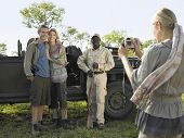 pic of  jeep  - Couple and safari guide posing by jeep while young woman taking photograph - JPG