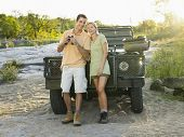 Full length of a smiling young couple standing by jeep with binoculars