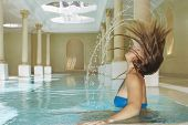 Side view of young woman flipping hair in swimming pool