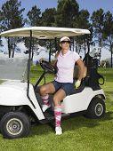 Hermosa golfista lleva gafas de sol, desembarcar del carrito de golf