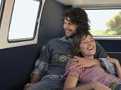 stock photo of campervan  - Smiling young couple enjoying road trip in campervan - JPG