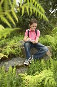 Happy young boy studying plants and writing on clipboard in forest