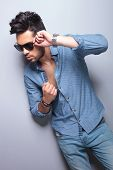 casual young man holding a hand on his sunglasses and the other on his unbuttoned shirt while looking away from the camera. on gray background