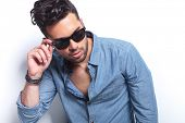 closeup of a casual young man holding a hand on his sunglasses while looking away from the camera. o