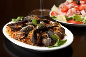 stock photo of antipasto  - Mussels dinner with red sauce and pasta and an antipasto salad. Shallow depth of field.