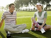 Full length of two young golfers sitting on golf course