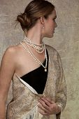 beautiful woman in gold shawl and black dress looking over her shoulder on grunge texture background