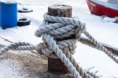 stock photo of bollard  - frozen ship cable under snow old bollard at the pier in winter - JPG