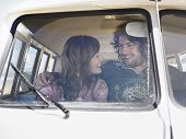 stock photo of campervan  - Smiling young couple looking at each other in campervan - JPG
