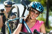 Serene sporty teens carrying their mountain bikes