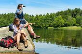 Caucasian teenage hikers birdwatching at lake