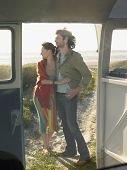 stock photo of campervan  - Full length of young couple embracing on beach view through campervan door - JPG