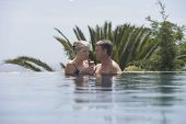 Happy mature couple drinking daiquiri in outdoor pool