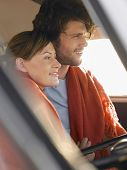 picture of campervan  - Loving young couple wrapped in blanket in front seat of campervan - JPG