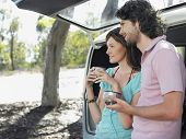 Happy young woman drinking coffee from thermos cups leaning in open tailgate of campervan