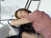 stock photo of campervan  - Tired young woman resting on steering wheel of van - JPG