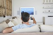 Rear view of middle aged man watching television in living room