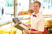 stock photo of cashiers  - Male cashier in a bakery posing with cash register - JPG
