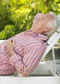Side view of a mature man reclining on lounge chair outdoors