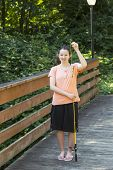 stock photo of brook trout  - Vertical photo of young girl holding up small trout while fishing off wooden bridge with trees and lamp post in background - JPG
