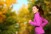Aspirations - Aspirational woman runner running looking and thinking about future goals. Female athlete jogging in autumn forest in fall color foliage. Beautiful multiracial Asian Caucasian jogger.
