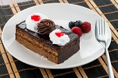 picture of custard  - Piece of chocolate cake with berries on white plate.