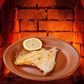 Fried Sole Fish On Plate And Hot Bricks Of Oven