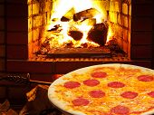 Pizza With Salami And Open Fire In Oven