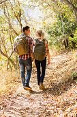 happy young couple walking in autumn forest