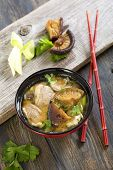 stock photo of duck breast  - Soup with duck breast and leeks in a red cup - JPG