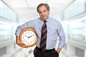 mature businessman holding a clock at the office
