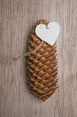 stock photo of home is where your heart is  - Heart shaped Christmas decoration and spuce cone on wooden table - JPG