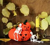 Halloween still life - pumpkin with  yellow leaves on the wooden background