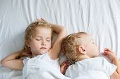 stock photo of matron  - charming little brother and sister asleep on white background - JPG