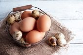 Many eggs in basket on wooden background