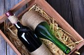 Bottles of wine in wooden box, on wooden background