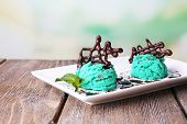 Tasty ice cream with chocolate decorations and sauce plate, on color wooden table, on bright backgro