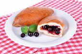 Fresh baked pasties with currant on plate on table close-up